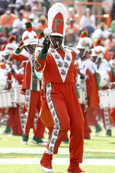 FILE -In this Oct. 8, 2011 file photo, Florida A&M Marching 100 Drum Major Robert Champion performs during a performance at halftime of the game against Howard University at Bragg Memorial Stadium in Tallahassee, Fla. Thirteen people were charged Wednesday, May 2, 2012, for their roles in the hazing death of Florida A&M university drum major who was severely beaten during a ritual, a prosecutor said. (AP Photo/Don Juan Moore)