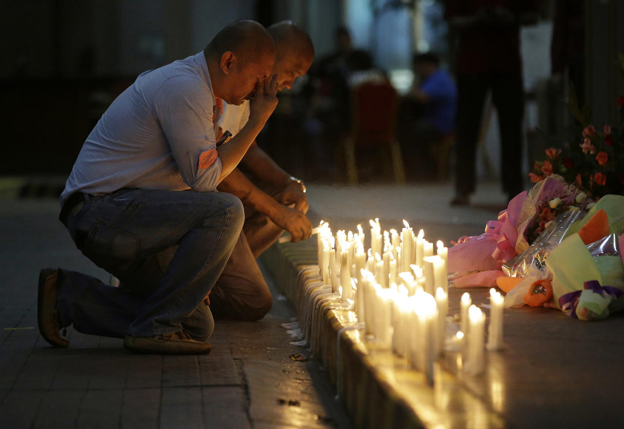 <p>A man holds back tears as he lights candles for victims in an attack at the Resorts World Manila complex, Friday, June 2, 2017, in Manila, Philippines. (Photo: Aaron Favila/AP) </p>