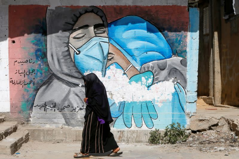 A Palestinian woman walks past a mural, amid COVID-19 outbreak, in the central Gaza Strip