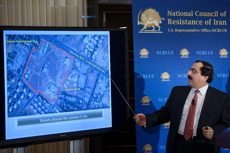 Alireza Jafarzadeh, Deputy Director of the Washington office of the National Council of Resistance of Iran, shows satellite photos during a press conference at the National Press Club February 24, 2015, in Washington, DC