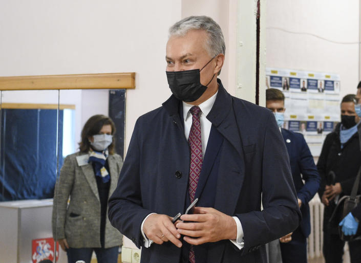 Lithuania's President Gitanas Nauseda, wearing face masks to protect against coronavirus, arrives at a polling station during the parliamentary elections in Vilnius, Lithuania, Sunday, Oct. 11, 2020. Polls opened Sunday for the first round of national election in Lithuania, where voters will renew the 141-seat parliament and the ruling four-party coalition is widely expected to face a stiff challenge from the opposition to remain in office. (Lithuanian President Office via AP)
