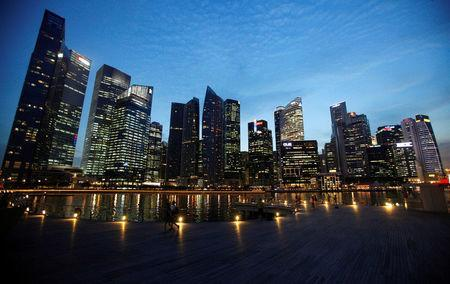 People walk past the skyline of Marina Bay central business district in Singapore April 26, 2013. REUTERS/Edgar Su/File Photo