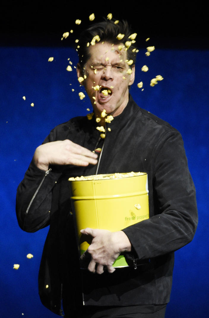 """Jim Carrey, a cast member in the upcoming film """"Sonic the Hedgehog,"""" throws popcorn onto his face during the Paramount Pictures presentation at CinemaCon 2019 in Las Vegas on April 4, 2019. (Photo by Chris Pizzello/Invision/AP)"""