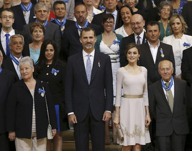 Spain's King Felipe VI and Queen Letizia pose with citizens decorated with the Order of Civil Merit during a handover ceremony at the Royal Palace in Madrid on June 19, 2015