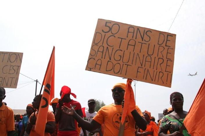 """""""50 years of bloody dictatorship, it has to finish"""" reads the sign, as protesters marched in Togo's capital Lome in January 2019 (AFP Photo/MATTEO FRASCHINI KOFFI)"""