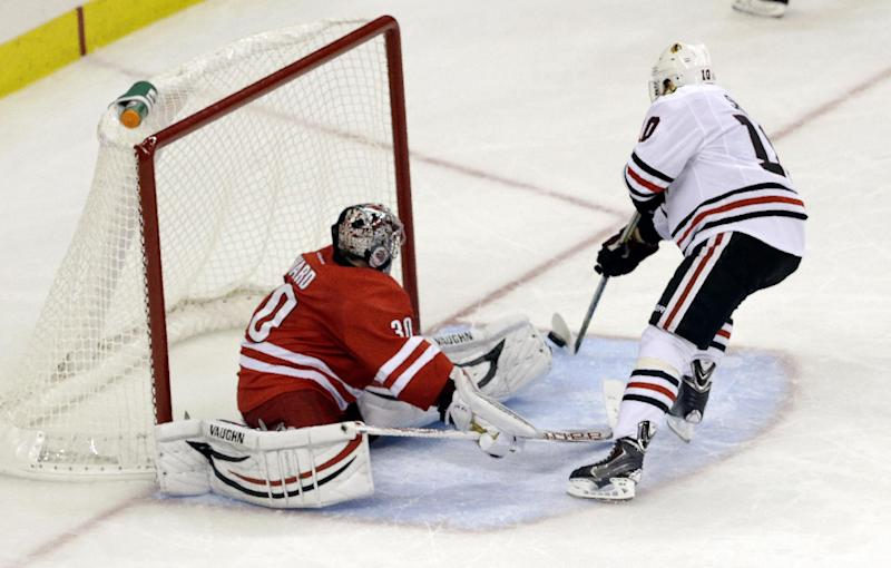 Chicago Blackhawks' Patrick Sharp, right, scores the game winning goal against the Carolina Hurricanes goalie Cam Ward during a shootout in an NHL hockey game in Raleigh, N.C., Tuesday, Oct. 15, 2013. Chicago won 3-2. (AP Photo/Gerry Broome)