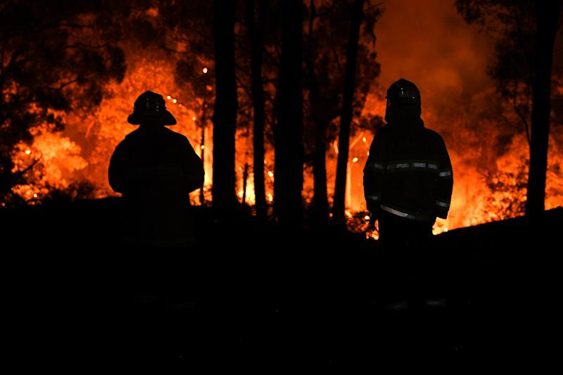 Pictured are two silhouettes of firefighters in front of bushfires in NSW.