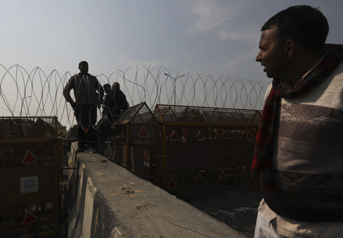Workers put barbwires on top of barricades to stop protesting farmer entering the capital Delhi, at the Delhi-Uttar Pradesh border, on the outskirts of New Delhi, India, Saturday, Jan. 30, 2021. Indian farmers and their leaders spearheading more than two months of protests against new agriculture laws began a daylong hunger strike Saturday, directing their fury toward Prime Minister Narendra Modi and his government. Farmer leaders said the hunger strike, which coincides with the death anniversary of Indian independence leader Mahatma Gandhi, would reaffirm the peaceful nature of the protests. (AP Photo/Manish Swarup)