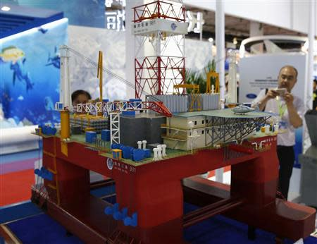A visitor takes a picture of a scale model of the Chinese oil rig Haiyang Shi You 981 during the China Beijing International High-Tech Expo in Beijing, May 16, 2014. REUTERS/Kim Kyung-Hoon