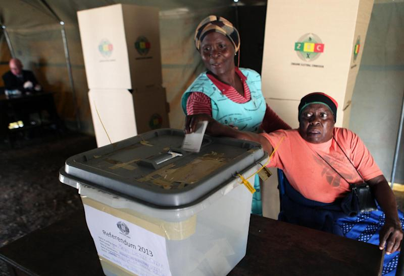 A woman is assisted to cast her vote during a referendum in Harare, Zimbabwe, Saturday, March, 16, 2013. The country is holding the referendum on a new constitution which will pave way for the adoption of the draft constitution as the country prepares to hold elections later in the year. (AP Photo/Tsvangirayi Mukwazhi)
