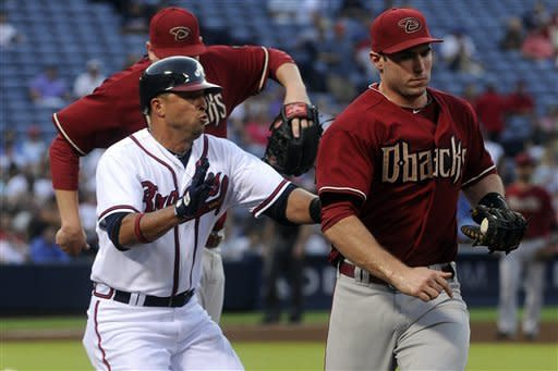 Atlanta Braves' Martin Prado, left, runs into Arizona Diamondbacks first baseman Paul Goldschmidt at first base after being forced out on a line drive during the fourth inning of a baseball game on Wednesday, June 27, 2012, in Atlanta. (AP Photo/John Amis)