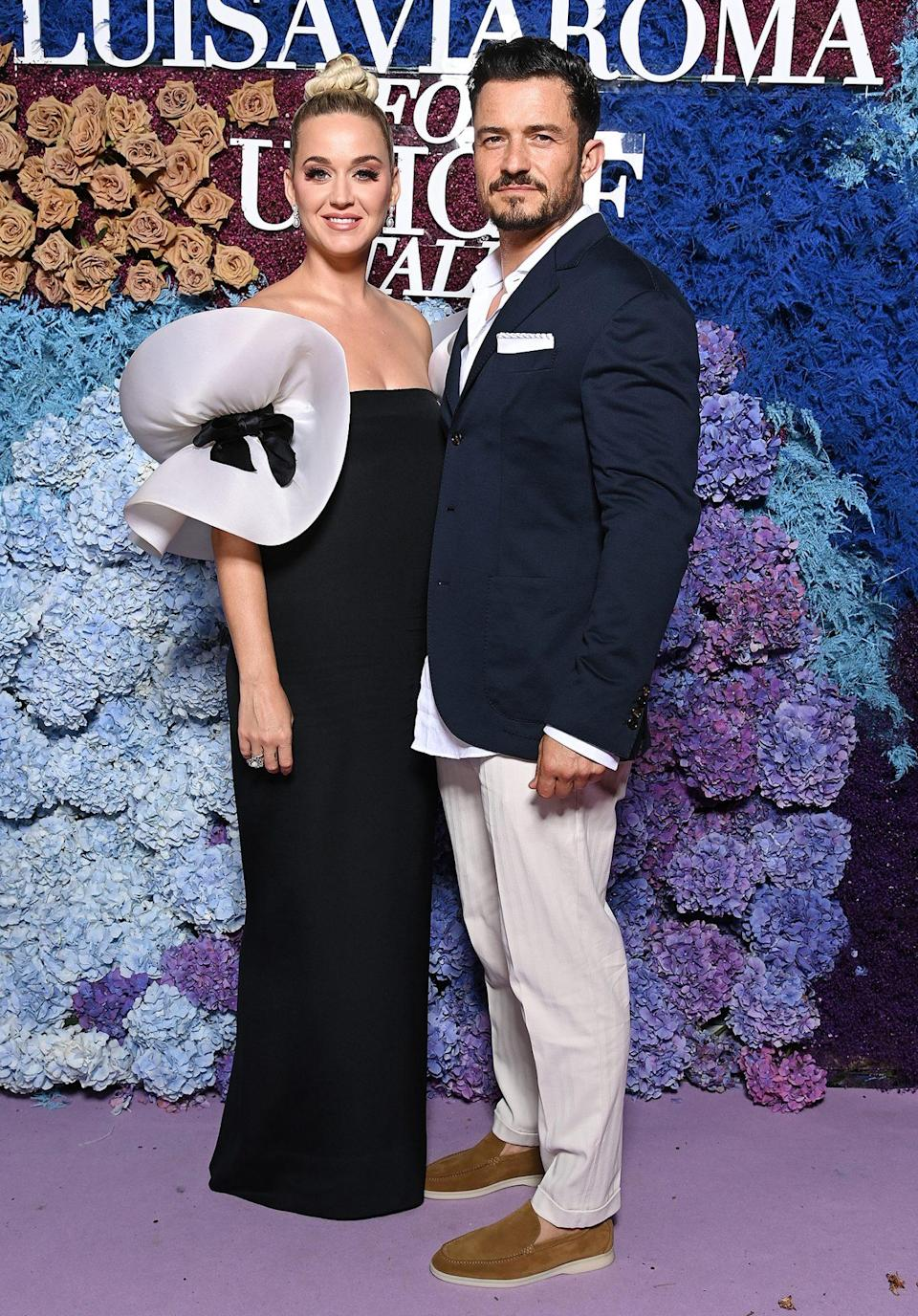 <p>have a date night on the red carpet! Katy wears a vintage Pierre Cardin column gown with voluminous sleeves and Buccellati jewels, while Orlando wears a navy jacket, white pants and brown loafers. </p>
