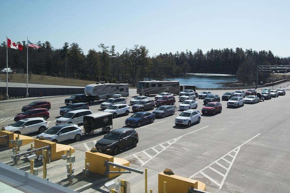 Vehicles wait at the Canadian border after the US/Canada border has been closed to all non-essential travel in Lansdowne, Ontario, on March 22, 2020. - The United States agreed with Mexico and Canada to restrict non-essential travel because of the coronavirus, COVID-19, outbreak and is planning to repatriate undocumented immigrants arriving from those countries. (Photo by Lars Hagberg / AFP) (Photo by LARS HAGBERG/AFP via Getty Images)