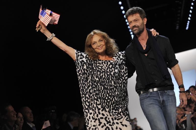 ADDS NAME OF PERSON ON RIGHT-   Designer Diane von Furstenberg waves American flags as she walks the runway with DVF creative director Yves Mispelaere, right, after the DVF Spring 2012 presentation during Fashion Week, Sunday, Sept. 11, 2011 in New York.   (AP Photo/Stephen Chernin)