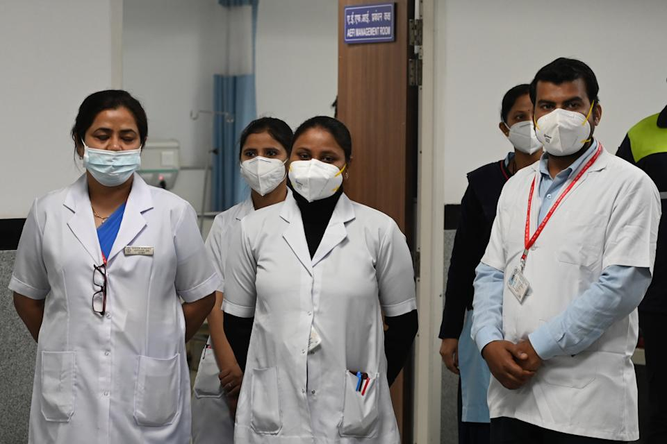 Health workers wait for the start of the Covid-19 coronavirus vaccination drive at the All India Institute of Medical Science (AIIMS) in New Delhi in January 16, 2021. (Photo by Sajjad HUSSAIN / AFP) (Photo by SAJJAD HUSSAIN/AFP via Getty Images)