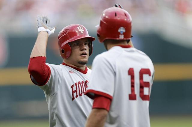 FILE - In this June 15, 2013, file photo, Indiana's Kyle Schwarber, left, celebrates with teammate Dustin DeMuth (16) after scoring against Louisville in an NCAA College World Series game in Omaha, Neb. Indiana's rise in baseball has been no surprise to the Big Ten. After the Hoosiers' historic 2013 season, the rest of the nation is now aware of the powerful program Tracy Smith has built. (AP Photo/Nati Harnik, File)