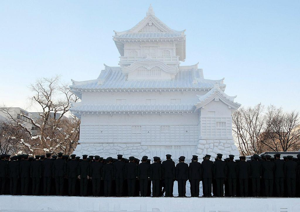 Members of Japan's Self Defence Force stand in front of a snow castle at Odori Park on February 4, 2008 in Sapporo, Japan.
