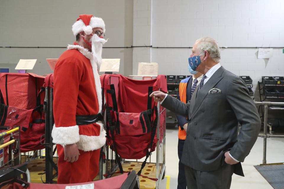 CIRENCESTER, ENGLAND - DECEMBER 18: Prince Charles, Prince of Wales, wearing a mask speaks to postal worker Tim Lafford (L) wearing a Father Christmas outfit during a visit to the Royal Mail's Delivery Office in Cirencester to recognise the vital public services that the country's postal workers provide, especially during the coronavirus pandemic and in the run-up to Christmas on December 18, 2020 in Cirencester, England.  (Photo by Geoff Caddick - WPA Pool / Getty Images)