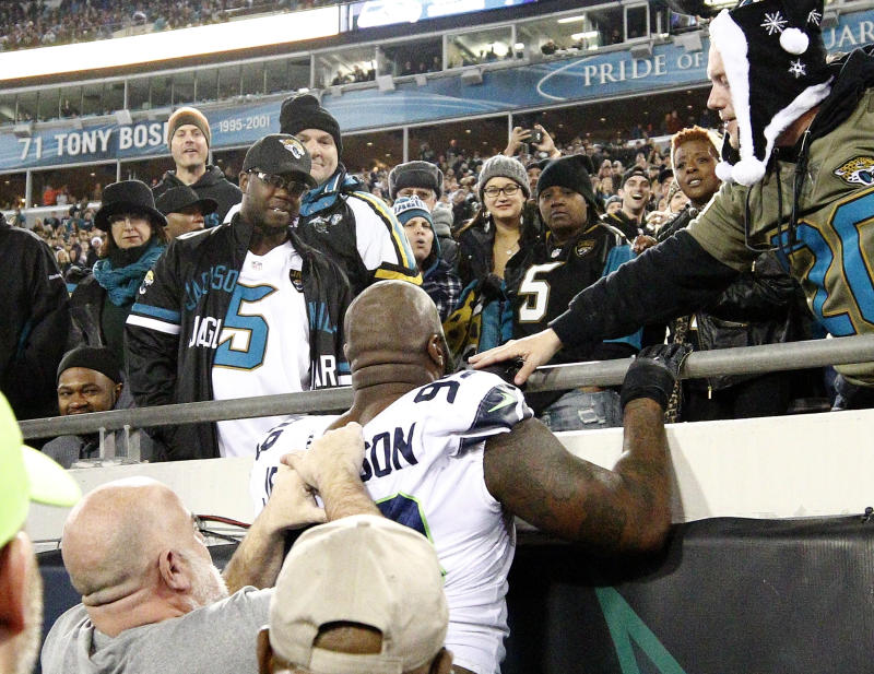 Seattle Seahawks defensive tackle Quinton Jefferson, center, tries to climb up in the stands after Jacksonville Jaguars fans threw objects at him. (AP)