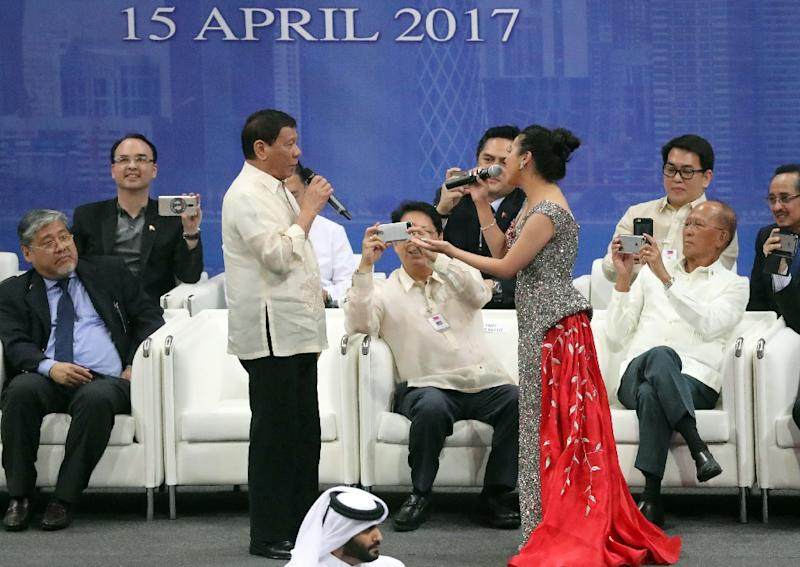 Rodrigo Duterte (L), President of the Philippines, sings a duet with singer Hanna Uddin during a gathering at Lusail Sports Arena in Lusail, 20km north of the Qatari capital on April 15, 2017