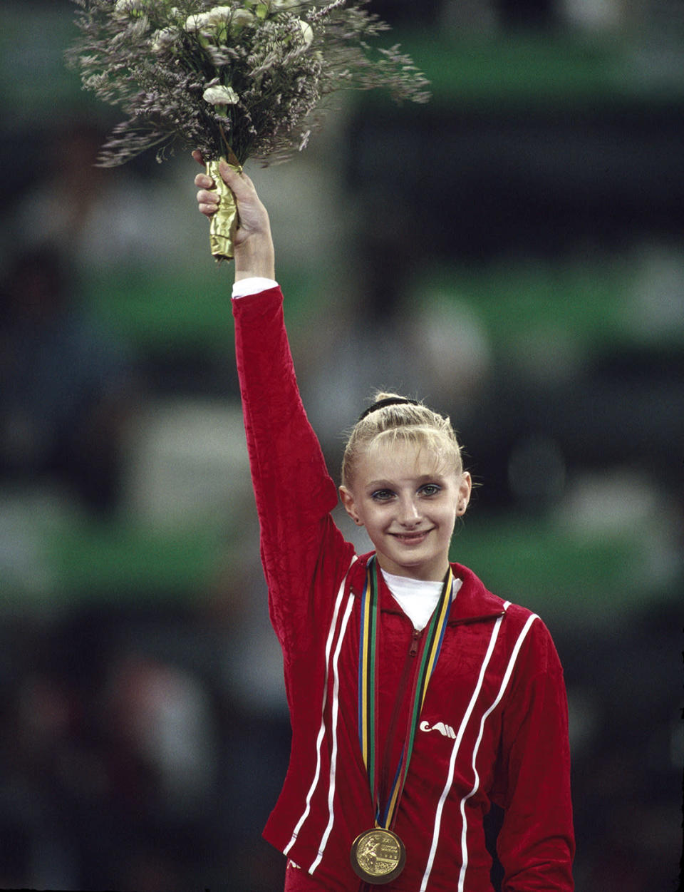 <p>Ukranian gymnast Tatiana Gutsu of the Unified Team (formerly Soviet Union) celebrates on the medal podium after receiving her gold medal at the 1992 Summer Olympics in Barcelona. (Photo by Bob Thomas/Getty Images) </p>
