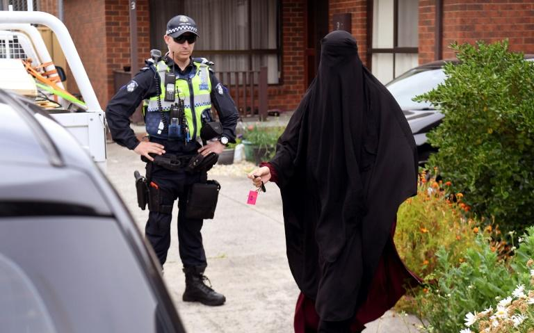 A woman was seen leaving a Melbourne house which police raided after three men were arrested for allegedly plotting terror attacks in the city
