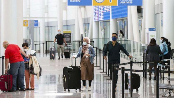 PHOTO: In this July 5, 2021, file photo, travelers wearing face masks walk out of the arrivals hall at Toronto Pearson International Airport in Mississauga, Ontario, Canada. (Chine Nouvelle/SIPA via Shutterstock, FILE)