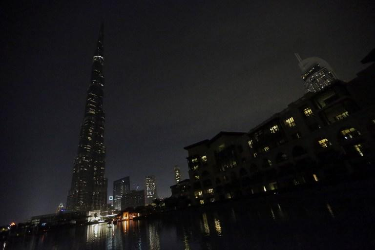 """The lights on the Burj Khalifa tower (L) are switched off for an hour in Downtown Dubai, on March 23, 2013, as iconic landmarks and skylines are plunged into darkness as the """"Earth Hour"""" switch-off of lights around the world got under way to raise awareness of climate change. AFP PHOTO/KARIM SAHIB"""