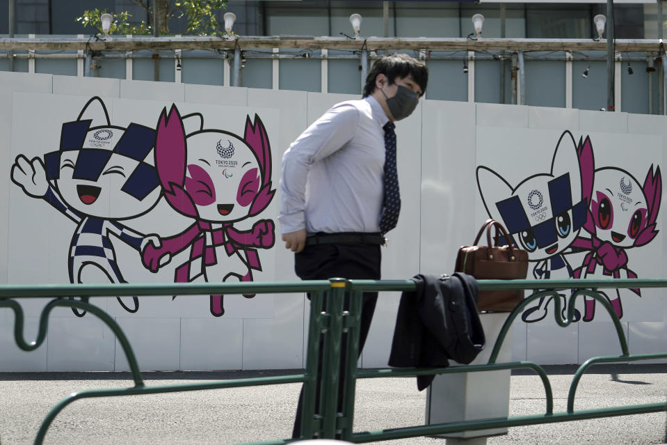 A man wearing a protective mask to help curb the spread of the coronavirus stands near drawings of Miraitowa and Someity, official mascots for the Tokyo 2020 Olympics and Paralympics, on a construction wall Tuesday, April 20, 2021, in Tokyo. (AP Photo/Eugene Hoshiko)