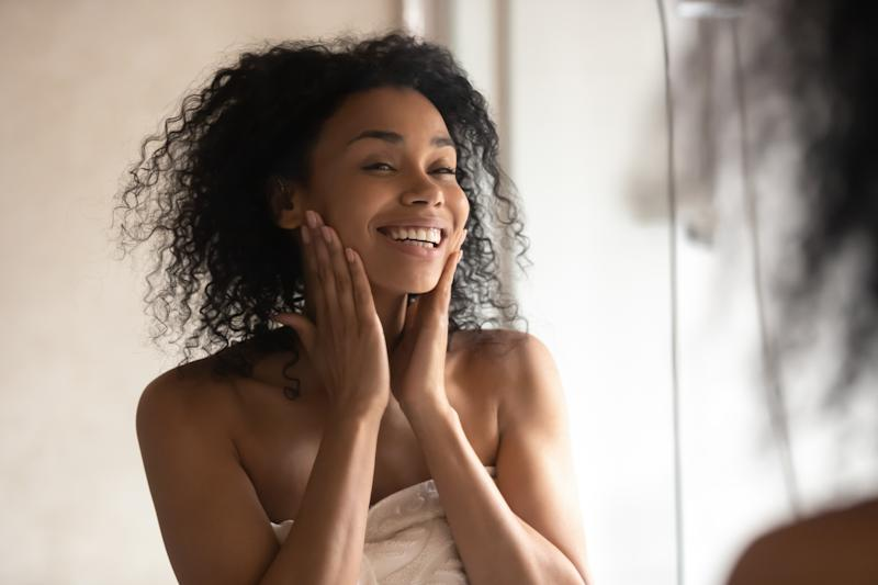 Close up black woman after shower stands wrapped in towel look in mirror touch gentle skin feels happy after cleansing mask, prevention protection, antiaging treatment usage and natural beauty concept