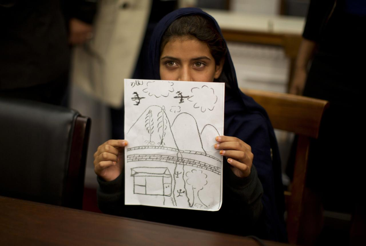 RNPS - PICTURES OF THE YEAR 2013 - Nabila Rehman, 9, holds up a picture she drew depicting the U.S. drone strike on her Pakistan village which killed her grandmother Mammana Bibi, at a news conference on Capitol Hill in Washington October 29, 2013. Nabila and her father and brother attended the news conference to highlight the personal costs in collateral damage for civilians killed and injured in the U.S. drone strike program. REUTERS/Jason Reed (UNITED STATES - Tags: POLITICS MILITARY TPX)
