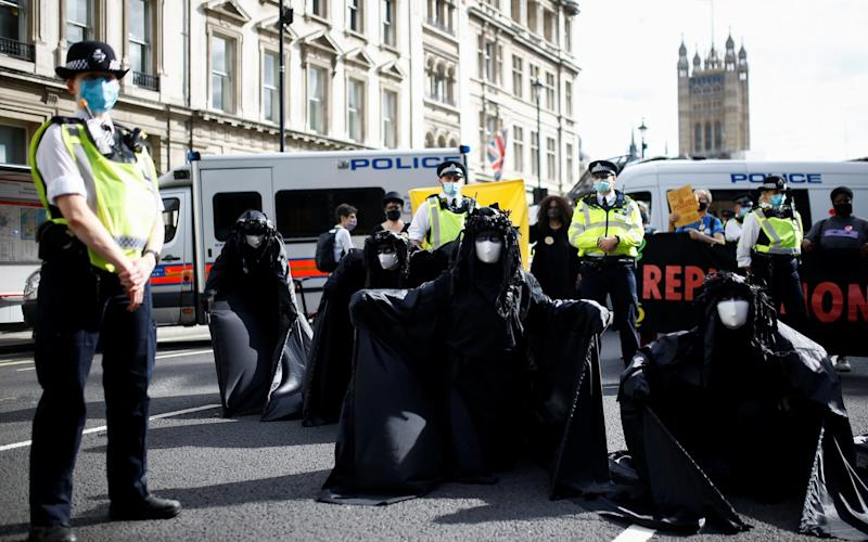 Police officers stand next to activists taking part in an Extinction Rebellion protest in Westminster, on September 8, 2020 - HENRY NICHOLLS/ REUTERS