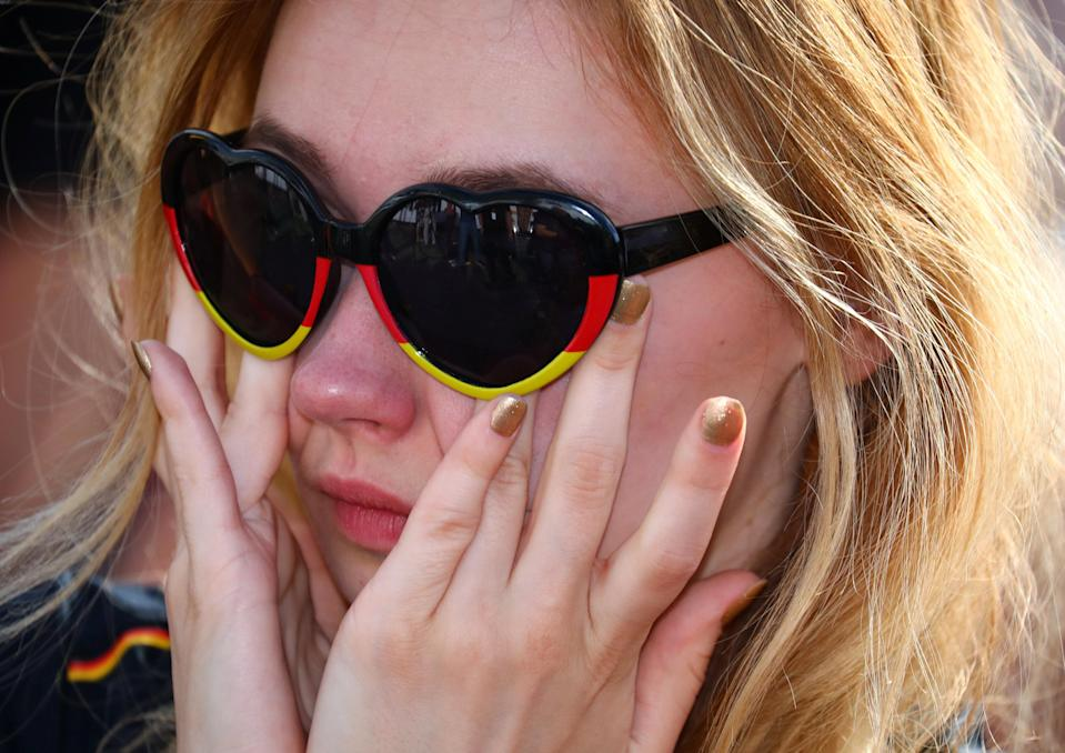 <p>A Germany fan reacts as she watches the match at a public viewing area at Brandenburg Gate. REUTERS/Hannibal Hanschke </p>