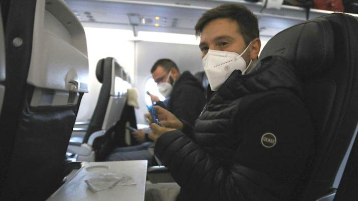 A man wearing a face mask sitting on a plane about to depart from Heathrow Airport