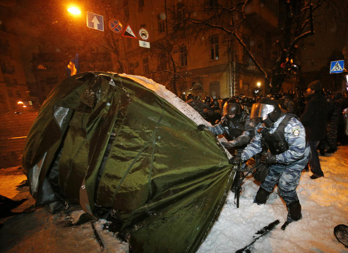 Riot police dismantle a tent while displacing pro-European Union activists from their barricades at the Ukrainian presidential administration building in Kiev, Ukraine, Tuesday, Dec. 10, 2013. Heavily armed riot troops broke into the offices of a top Ukrainian opposition party in Kiev and seized its servers Monday, the party said, as anti-government protests crippled the capital for yet another day. Elsewhere police dismantled or blocked off several small protest tent camps set up near key national government buildings in the city. (AP Photo/Alexander Zemlianichenko)