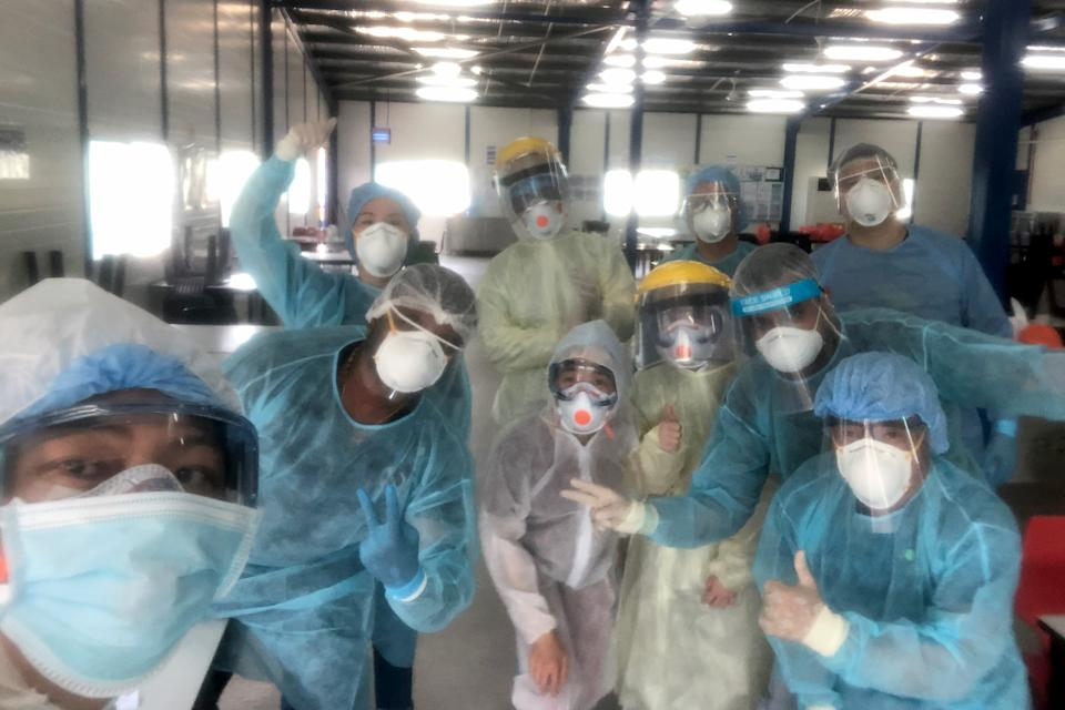 Dr Terry Teo (far left) and his fellow volunteers in protective gear at a swabbing area. (Photo courtesy of Dr Terry Teo)