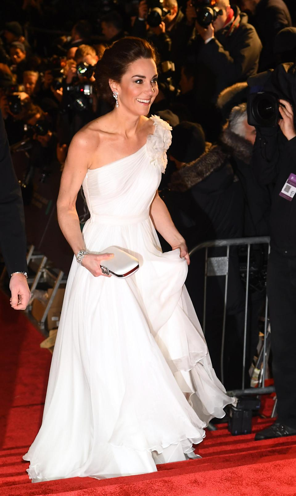 Kate channelled Hollywood glamour in a one-shoulder Alexander McQueen gown with floral on one side, to accompany William to the BAFTAs at The Royal Albert Hall. The Duchess teamed it with a new pair of Jimmy Choo's glittery Romy pumps and an Alexander McQueen satin clutch bag. She debuted Princess Diana's diamond and south sea pearl dangle earrings and borrowed the diamond quatrefoil bracelet, which once belonged to the Queen Mother. [Photo: Getty]