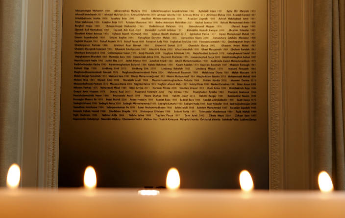 Candles burn in front of a plaque with the names of the victims of flight PS752, at the High Commission of Canada in London, Thursday, Jan. 16, 2020. The Foreign ministers of Canada, The Netherlands, Sweden, Ukraine and Afghanistan are meeting as part of the International Coordination and Response Group for the families of the victims of PS752 flight crashed shortly after taking off from the Iranian capital Tehran on Jan. 8, killing all 176 passengers and crew on board. (AP Photo/Frank Augstein)