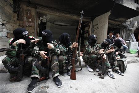 """Female members of the """"Mother Aisha"""" battalion sit together along a street in Aleppo's Salaheddine district"""