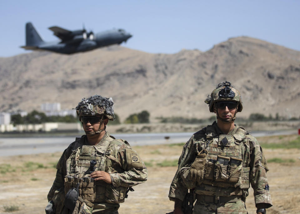 In this image provided by the Department of Defense, two paratroopers assigned to the 1st Brigade Combat Team, 82nd Airborne Division conduct security while a C-130 Hercules takes off during a evacuation operation in Kabul, Afghanistan, Wednesday, Aug. 25, 2021. (Department of Defense via AP)