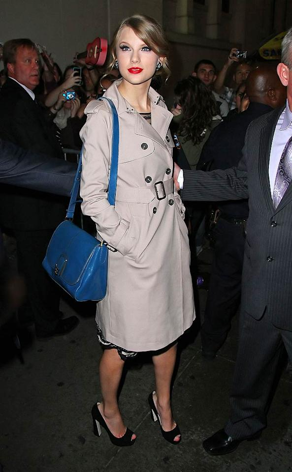 Taylor Swift jazzed up her belted khaki trench with a bright blue handbag and ruby red lips. (10/13/2011)