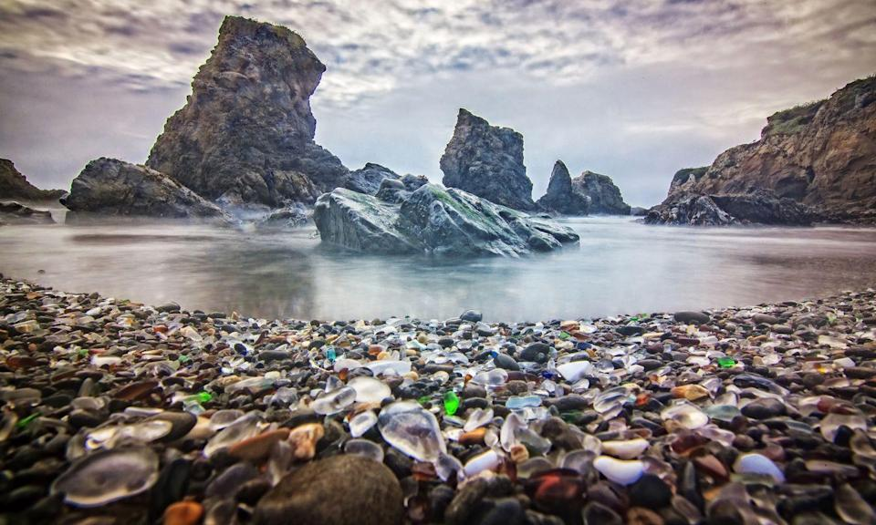 """<p>It's a nice treat to spot a piece of sea glass along the shoreline, but an entire shoreline of sea glass? That's something only MacKerricher's <a href=""""https://www.mendocino.com/glass-beach.html"""" rel=""""nofollow noopener"""" target=""""_blank"""" data-ylk=""""slk:Glass Beach"""" class=""""link rapid-noclick-resp"""">Glass Beach</a> in Fort Bragg, California has to offer. Despite an old fisherman's tale about the glass being """"<a href=""""https://www.mendocino.com/glass-beach.html"""" rel=""""nofollow noopener"""" target=""""_blank"""" data-ylk=""""slk:mermaid tears"""" class=""""link rapid-noclick-resp"""">mermaid tears</a>"""" that washed to shore, the abundance of shiny, smooth treasures is actually the result of the beach's proximity to an old dump. That's right, smooth. The tumultuous ocean waves and whipping winds render the sharp shards nice and smooth.</p>"""