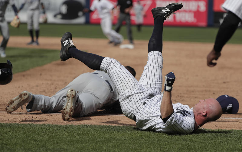 New York Yankees' Brett Gardner, right, falls to the ground after colliding with Tampa Bay Rays first baseman Rickie Weeks after Weeks reached for an errant throw by pitcher Xavier Cedeno during the sixth inning of a baseball game, Wednesday, April 12, 2017, in New York. Chase Headley scored on the play. Both Weeks and Gardner left the game. (AP Photo/Julie Jacobson)