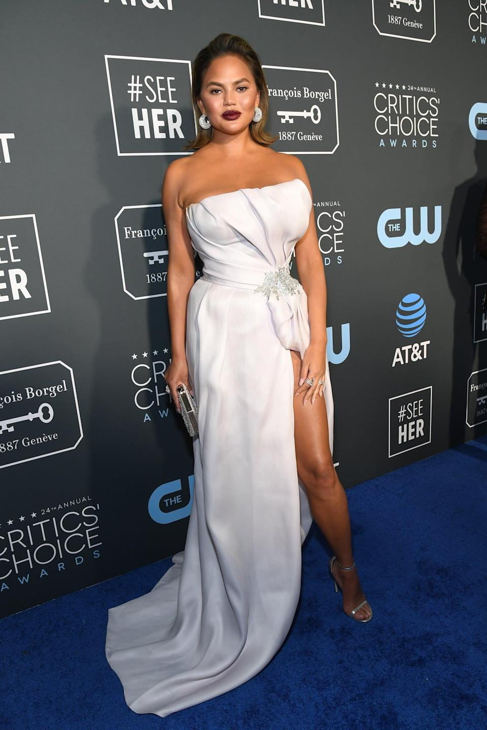 <p>Chrissy Teigen wearing a strapless white gown with a thigh-high slit by Maison Yeya, Jaipur Gems, and Stuart Weitzman heels.</p>