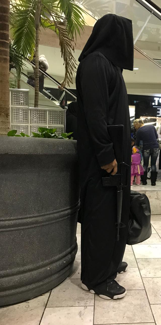 A man in a hooded costume, wielding what looked like a real firearm, spooked several people at an Omaha, Neb., mall this Halloween weekend. (Photo: Facebook)