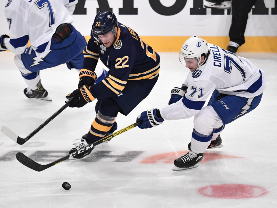 Buffalo Sabres' Johan Larsson (22) and Tampa' Bay Lightning Anthony Cirelli (71) go after the puck during an NHL hockey game in Globen Arena, Stockholm Sweden. Friday. Nov. 8, 2019. (Anders Wiklund/TT via AP)