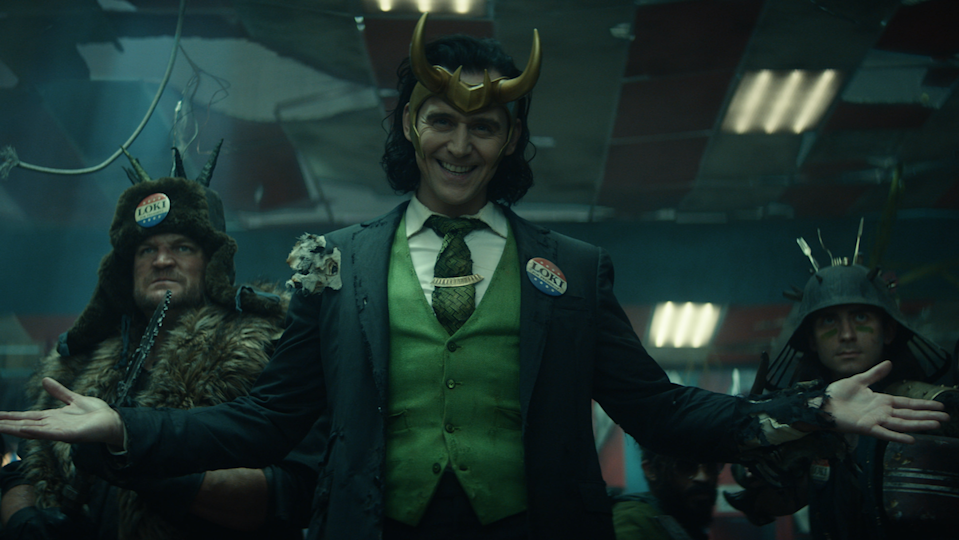 Loki wears his horned helmet and a three-piece suit before his army.