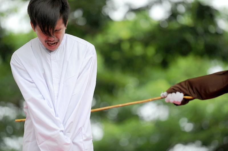 One of two Indonesian men is publicly caned for having gay sex in Aceh in May last year. Police in the province have now forcibly cut the hair of a group of transgender women