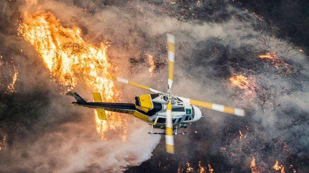 PHOTO: A Los Angeles County Fire helicopter flies over the Skirball Fire which began early morning in Bel-Air, Calif., Dec. 6, 2017. (John Cetrino/EPA)