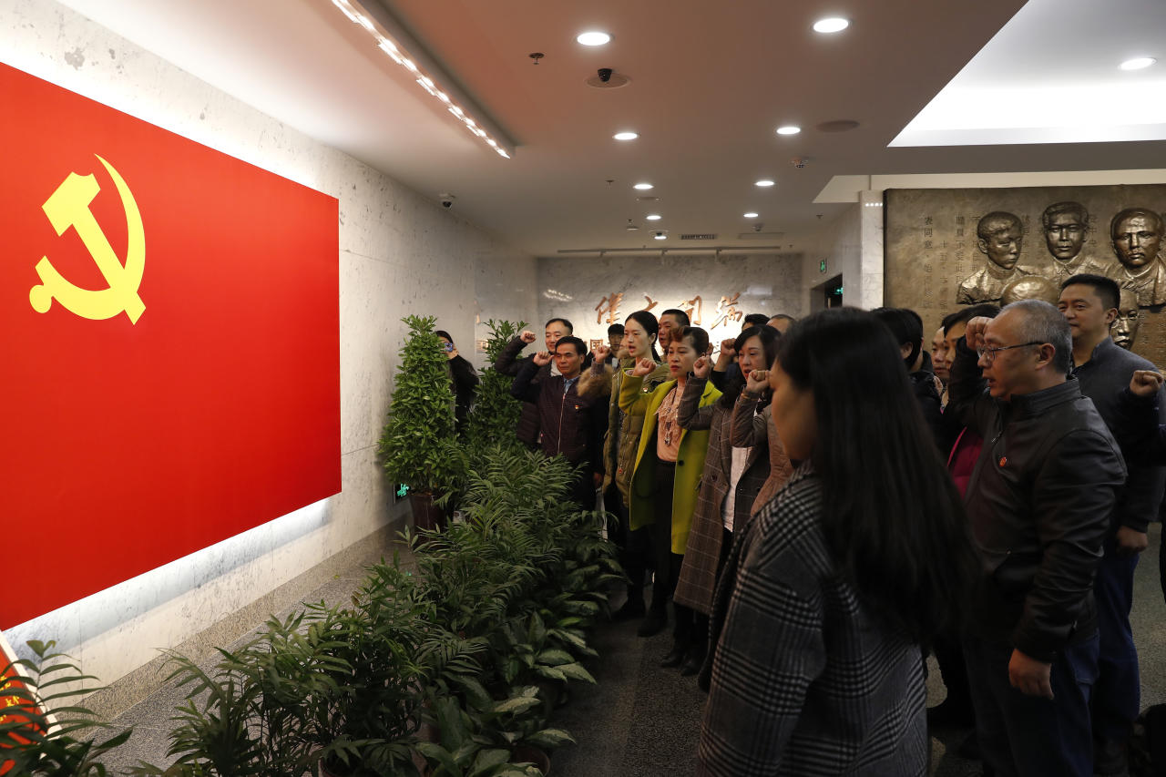 A group of Chinese visitors raise their fists take the oath in front of a Communist flag on display at the museum of the first National Congress of the Communist Party of China in Shanghai, China, Sunday, Nov. 19, 2017. Chinese tourists and visitors have flocked to the museum in Shanghai since President Xi Jinping made a visit with the newly-installed line-up of top party leaders late last month. During the leaders' visit, they were depicted on state television reaffirming their party oaths with their fists raised. (AP Photo/Andy Wong)